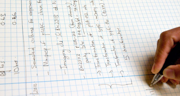 A Biotechnology Training Program Trainee writes in a lab notebook