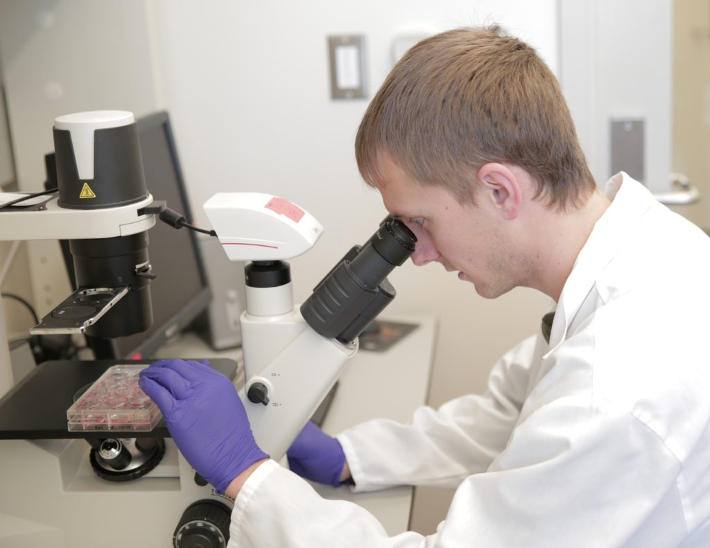 Photo of biomedical engineering graduate student Jared Carlson-Stevermer observes real-time CRISPR/Cas9 gene editing